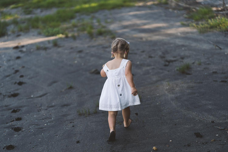 niña de espaldas caminando por la playa